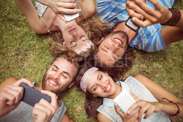 Hipsters lying on grass using smartphones Stock photo © wavebreak_media