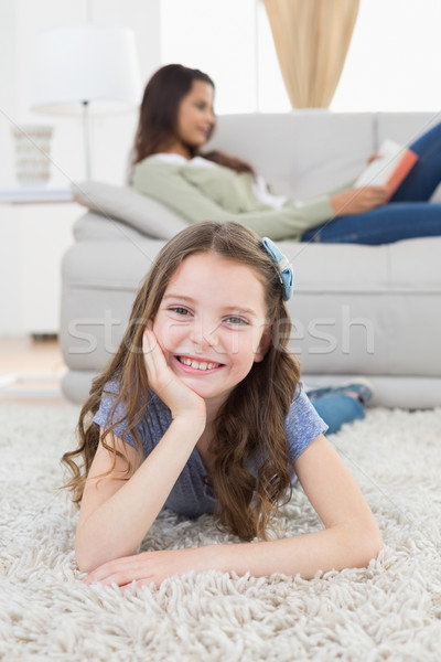 Happy girl lying on rug while mother relaxing at home Stock photo © wavebreak_media