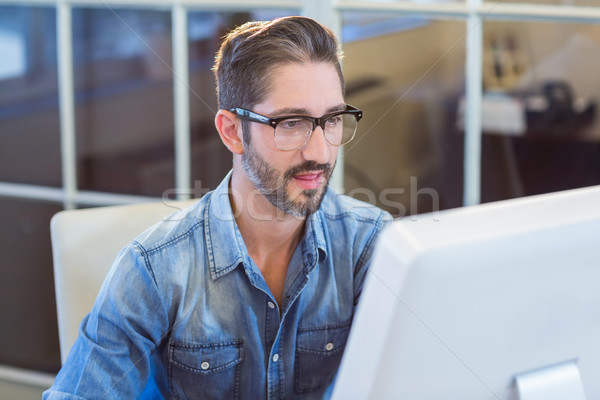 Casual businessman looking at computer screen Stock photo © wavebreak_media