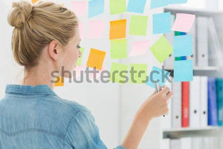 Nadenkend zakenvrouw naar sticky notes venster kantoor Stockfoto © wavebreak_media