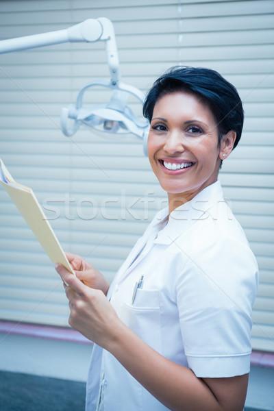 Sorridente feminino dentista leitura relatórios retrato Foto stock © wavebreak_media