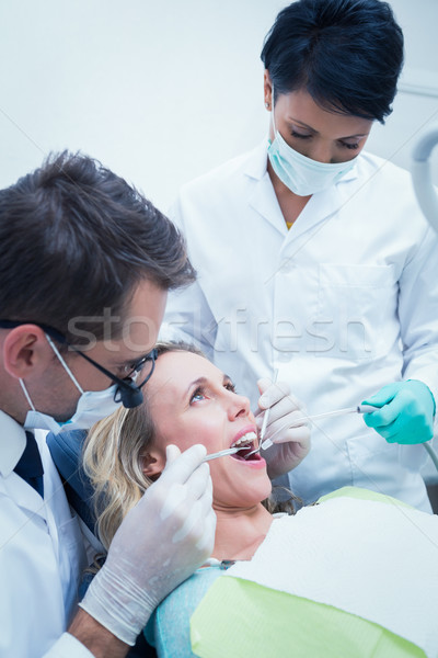 Stock photo: Male dentist with assistant examining womans teeth