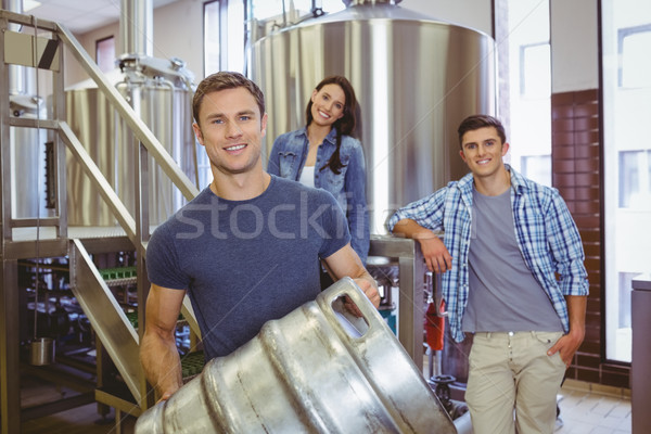 Young man holding keg with these colleagues behind him Stock photo © wavebreak_media