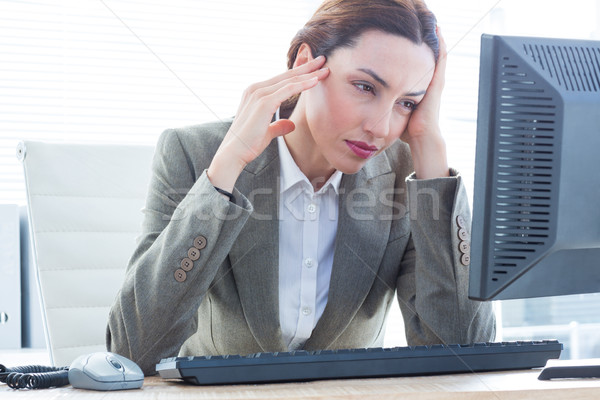 Upset business woman with head in hands in front of computer at  Stock photo © wavebreak_media