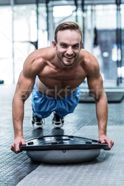 Muscular man doing bosu ball exercises Stock photo © wavebreak_media