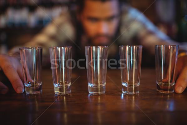 Waiter placing shot glasses on counter Stock photo © wavebreak_media