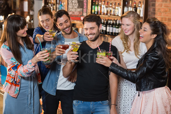 Happy friends toasting drink glasses Stock photo © wavebreak_media