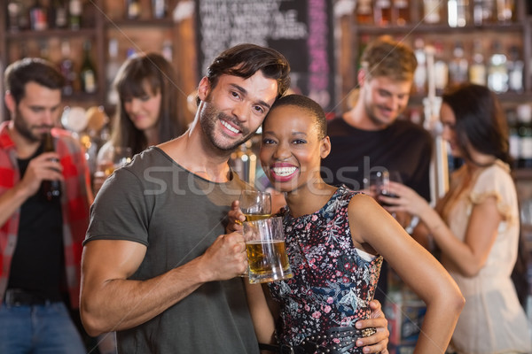 Portrait of young couple embracing while holding beer mugs Stock photo © wavebreak_media