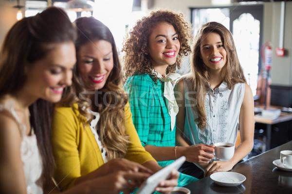 Friends using digital tablet while sitting in cafe Stock photo © wavebreak_media