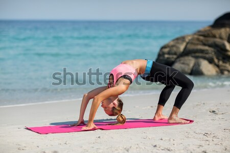 Stock photo: Young woman practicing yoga in bridge position at beach