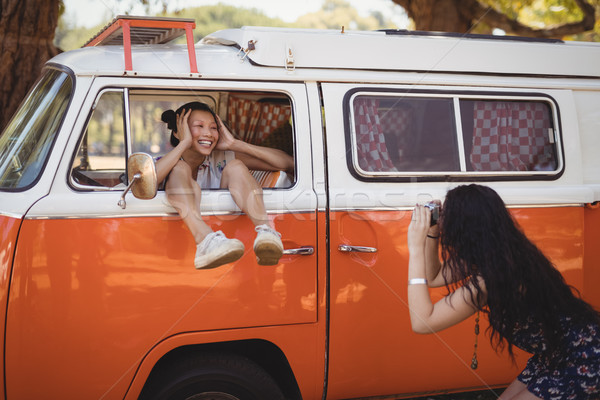 Woman photographing friend while standing by van Stock photo © wavebreak_media