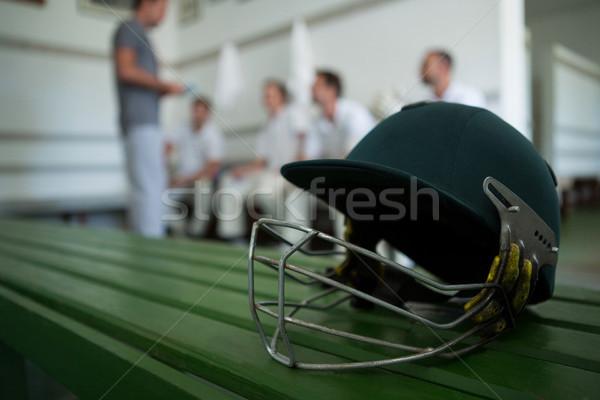 Close up of cricket helmet on table against team Stock photo © wavebreak_media