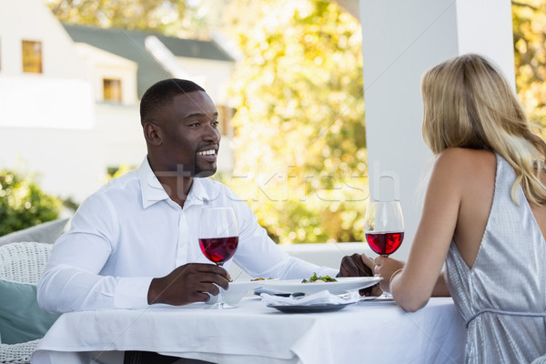 Stock photo: Young couple holding red wineglasses at restaurant