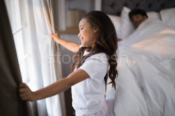 Side view of happy girl holding curtains in bedroom Stock photo © wavebreak_media