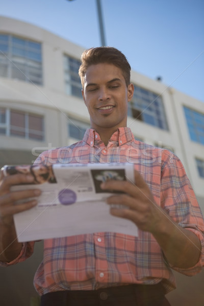 Stock photo: Low angle view of man reading paper while standing by building