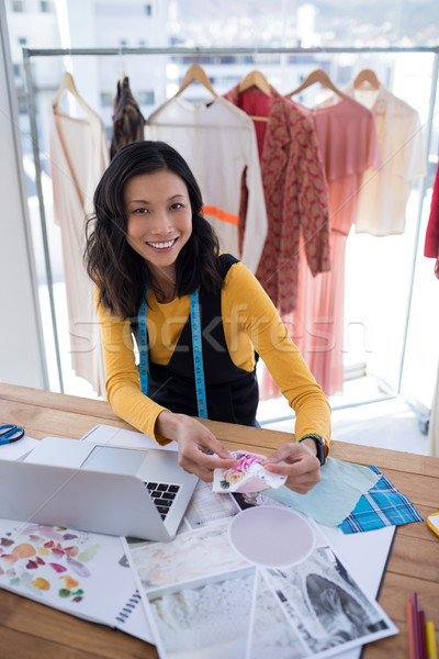 Female designer working on pieces of clothes in office Stock photo © wavebreak_media
