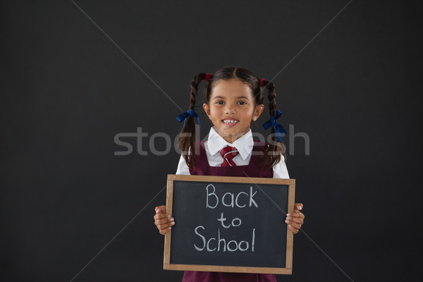Portrait of schoolgirl holding slate with text against blackboard Stock photo © wavebreak_media