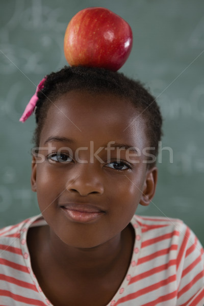 Schoolgirl sitting with red apple on her head against chalkboard Stock photo © wavebreak_media