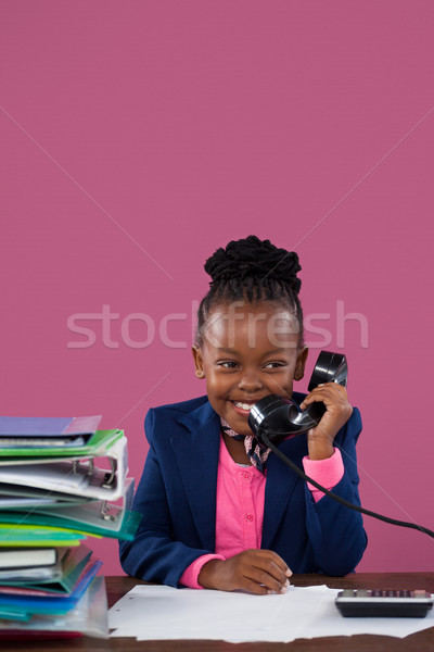 Smiling businesswoman talking on telephone while doing paperwork Stock photo © wavebreak_media