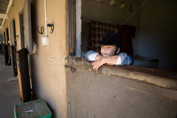 Stock photo: Girl leaning on wall in the stable