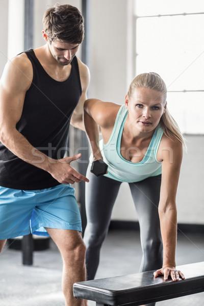 Sporty woman using dumbbells with personal trainor Stock photo © wavebreak_media
