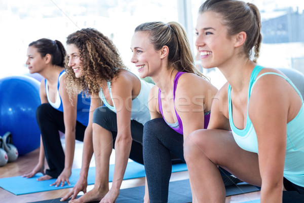 Cheerful woman in fitness studio doing lunge pose Stock photo © wavebreak_media