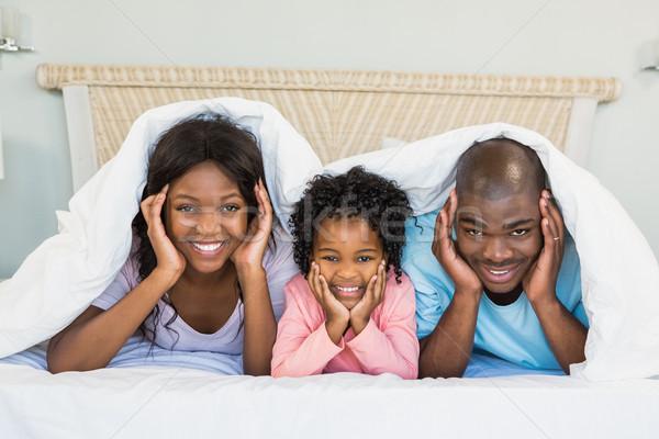 Happy family lying on bed Stock photo © wavebreak_media