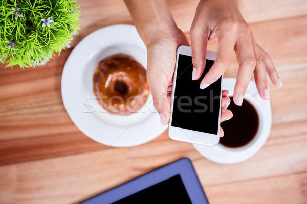 Overhead of feminine hands using smartphone Stock photo © wavebreak_media
