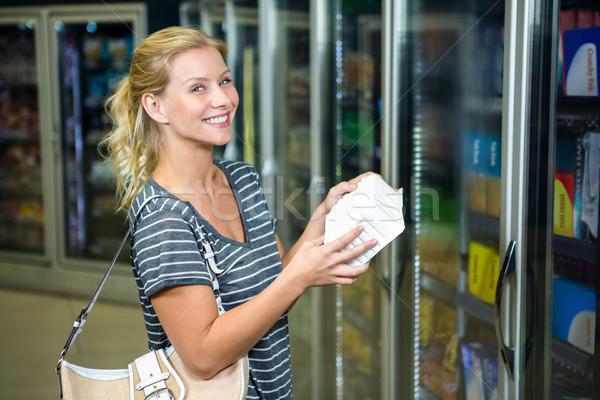 Blonde vrouw product glimlachend camera supermarkt Stockfoto © wavebreak_media