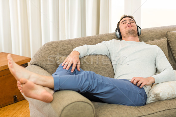 Young man feeling relaxed while listening to music Stock photo © wavebreak_media