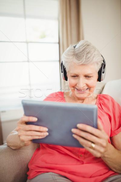 Feliz senior mulher ouvir música digital comprimido Foto stock © wavebreak_media
