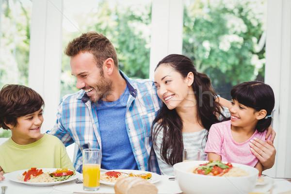 Sorridente família braço em torno de sessão mesa de jantar Foto stock © wavebreak_media