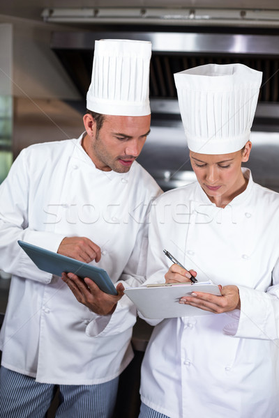 Focused chefs holding clipboards in kitchen Stock photo © wavebreak_media