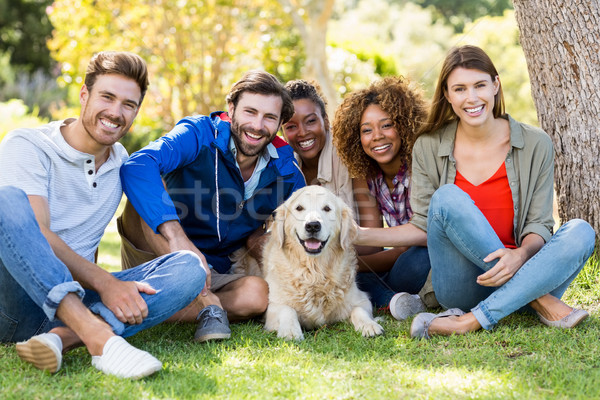 Group of happy friends sitting together with the dog Stock photo © wavebreak_media
