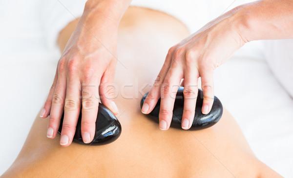 Cropped image of masseur giving hot stone massage on woman back Stock photo © wavebreak_media