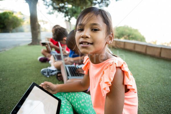 Girl with friends using digital tablet at park Stock photo © wavebreak_media