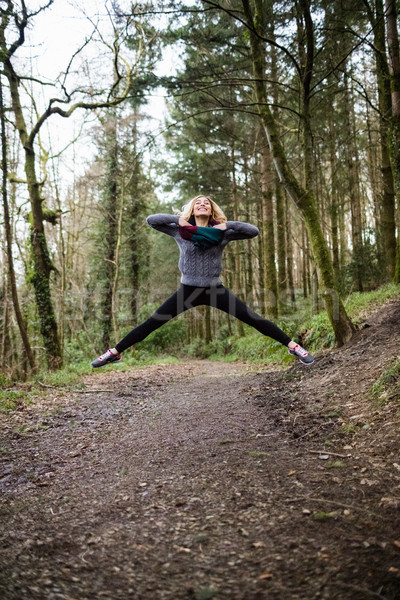 Belle femme sautant forêt belle femme souriante femme Photo stock © wavebreak_media