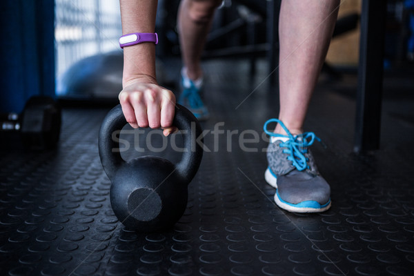 Low section of female athlete holding kettlebell in gym Stock photo © wavebreak_media