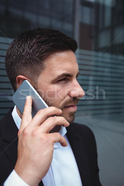 Empresário falante telefone móvel prédio comercial homem corporativo Foto stock © wavebreak_media