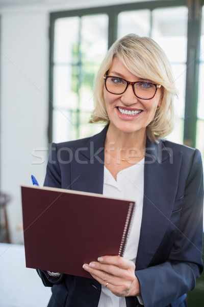 Businesswoman writing on diary in a restaurant Stock photo © wavebreak_media