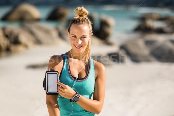 Young woman touching smartphone on armband Stock photo © wavebreak_media