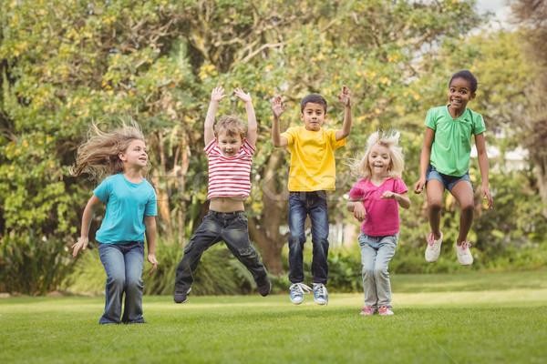 Mutlu sınıf arkadaşları atlama hava kız çim Stok fotoğraf © wavebreak_media
