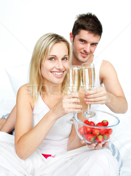 Couple toasting with champagne and strawberries to an engagement Stock photo © wavebreak_media