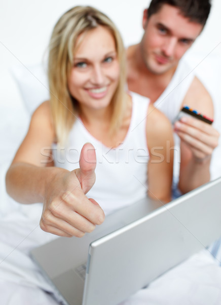 Couple in bed buying on-line successfully Stock photo © wavebreak_media