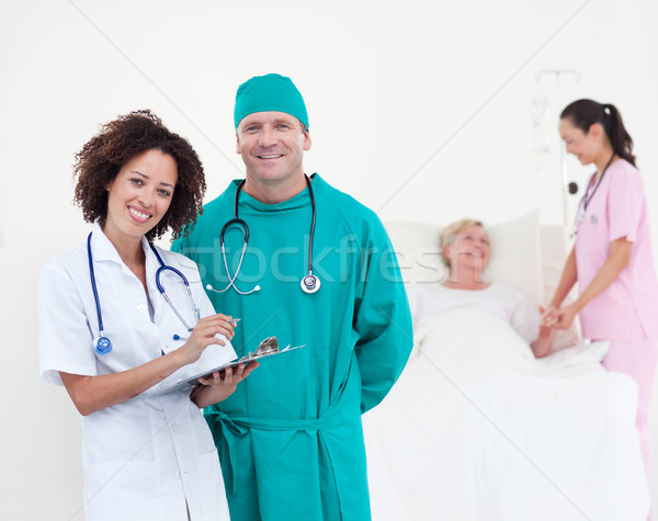 Charismatic team of doctors smiling at camera patient lying in her bed Stock photo © wavebreak_media