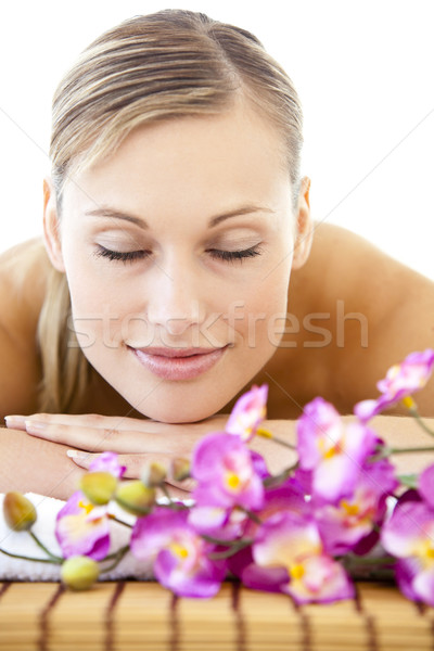 Portrait of a relaxed woman lying on a massage table in a spa center with flowers Stock photo © wavebreak_media