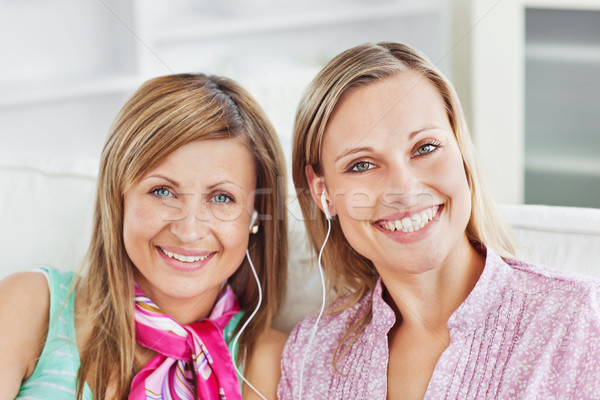 Captivating two female friends listen to music smiling at the camera sitting in the living-room Stock photo © wavebreak_media