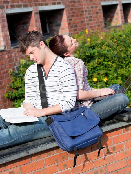 Pareja jóvenes estudiantes usando la computadora portátil lectura libro Foto stock © wavebreak_media