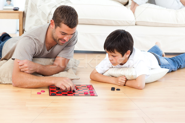 Handsome man playing checkers with his son lying on the floor at home Stock photo © wavebreak_media