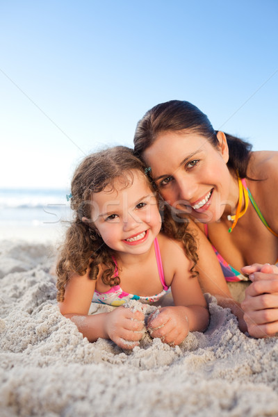 Mother and daughter lying down on the beach Stock photo © wavebreak_media